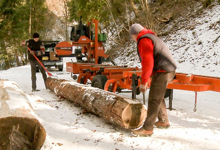 A hydraulic loader quickly uploads a log to the sawmill